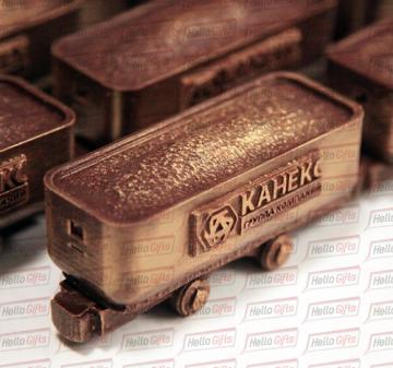 Механизмы и техника  из шоколада/ Подарки машиностроителям к Новому году и профессиональным праздникам     Шоколадная фигура «Вагонетка с логотипом компании» Габариты шоколадной фигуры Вагонетка 110 х 45 х 50 мм., вес 160-170 гр.  Бельгийский темный шоколад Barry Callebaut,  54%.  Упаковка: подарочный пенал из дерева с полноцветной прямой печатью (брендирование).  Размер упаковки: 140 х 65 х 80 мм.
